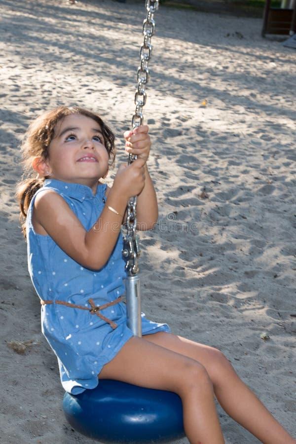 Fille ayant l'amusement sur une ligne de fermeture éclair de terrain de jeu le jour d'été photos stock