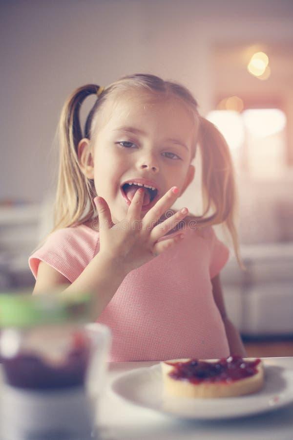 Fille ayant l'image haute étroite de petit déjeuner images libres de droits