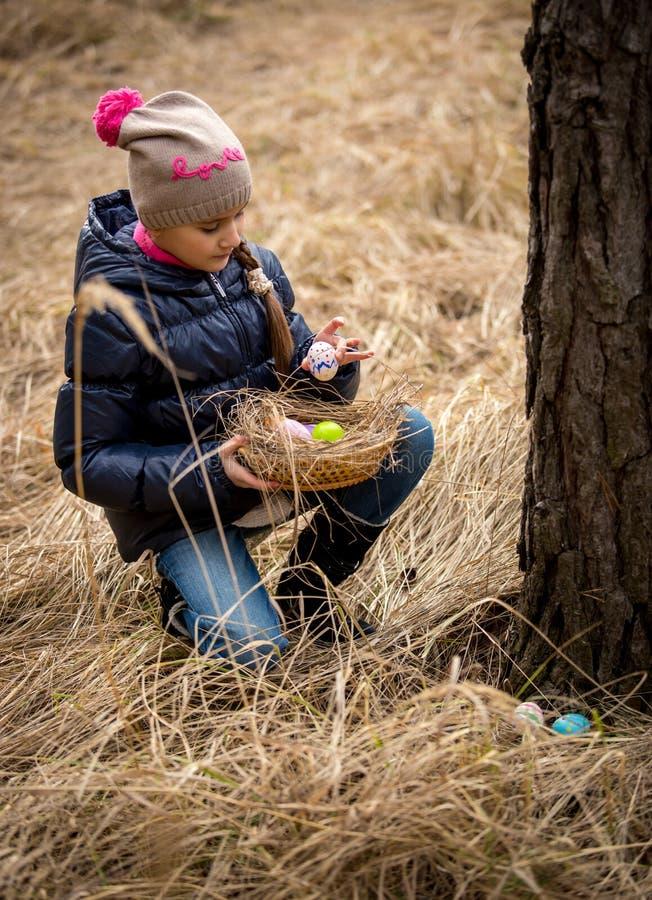 Fille ayant la chasse à oeuf de pâques à la forêt images stock