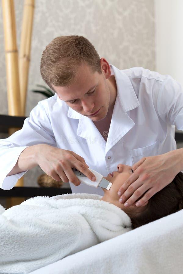 Fille ayant une peau professionnelle de nettoyage avec l'équipement d'ultrason image libre de droits