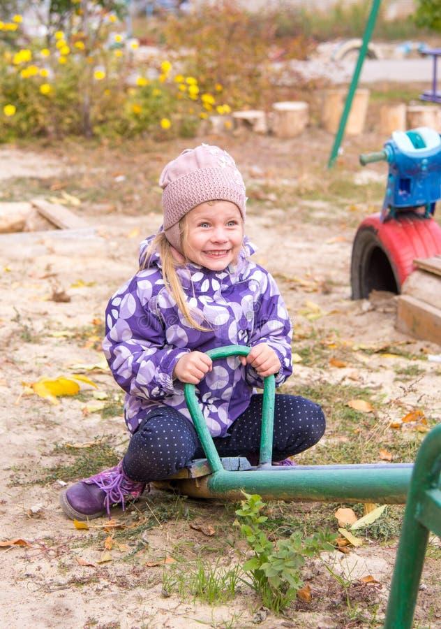 fille balançant heureusement sur une oscillation dans la cour photos stock