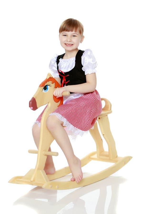 Fille balançant sur un cheval en bois images stock