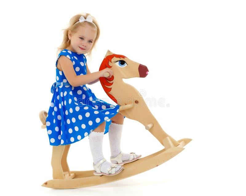 Fille balan?ant sur un cheval en bois images libres de droits