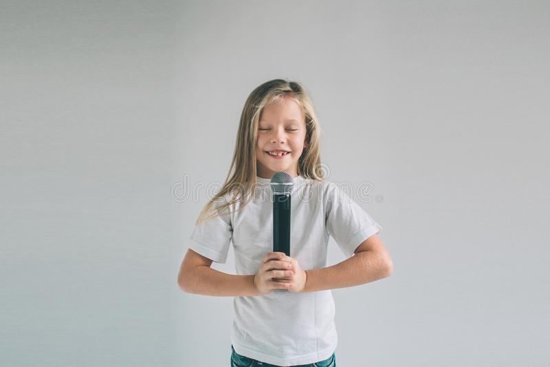 Fille basculant  Image d'un enfant chantant au microphone, d'isolement sur la lumière Portrait émotif d'un enfant attirant photo stock