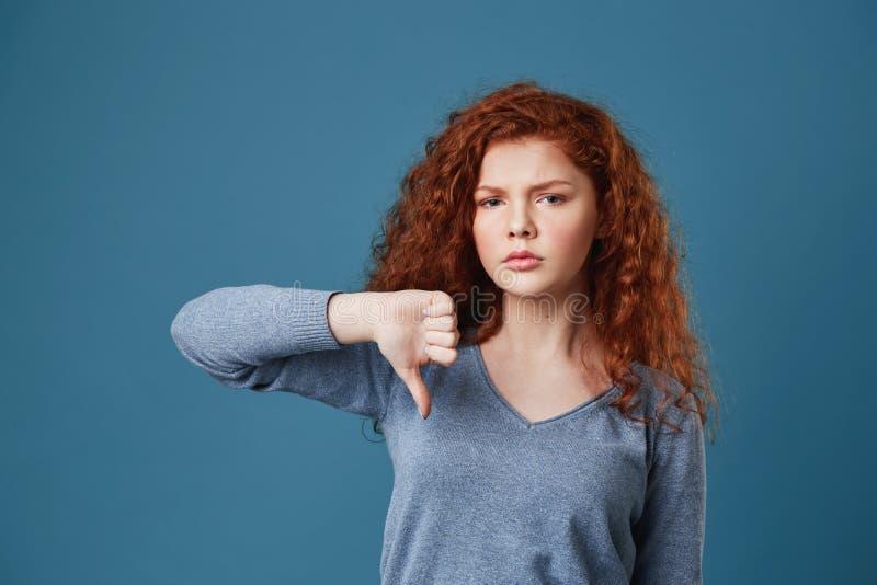 Fille belle malheureuse avec les cheveux bouclés rouges et les taches de rousseur regardant l'appareil-photo avec l'expression tr image libre de droits