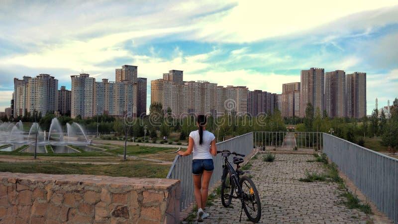 Fille, bicyclette et ville d'Astana photos libres de droits