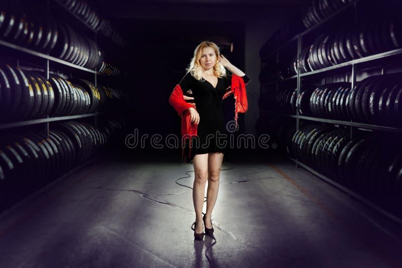 Fille blanche dans la robe noire et l'écharpe rouge avec des piles de pneu à l'arrière-plan images libres de droits