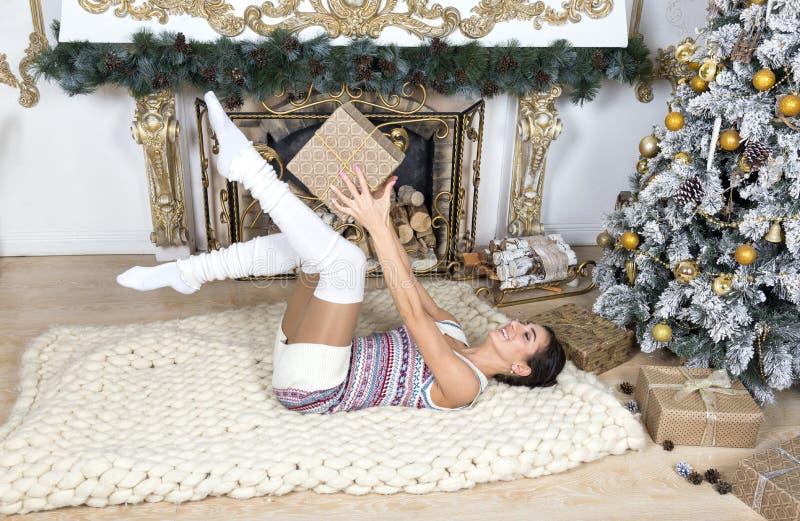 1 fille blanche se trouvant sur une couverture blanche près des WI d'arbre de Noël images stock