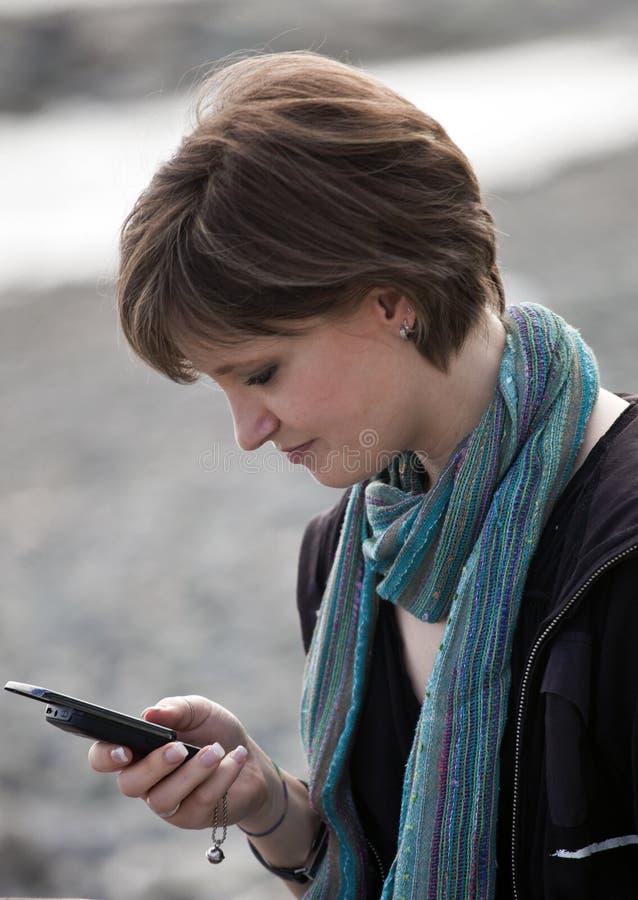 Fille blonde à l'aide de son téléphone photos libres de droits