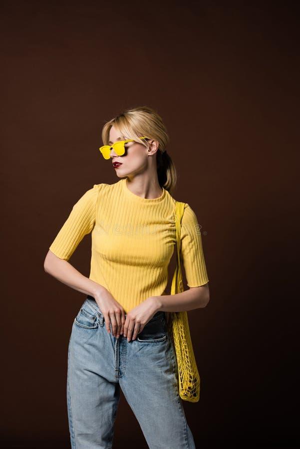 fille blonde élégante avec le sac de ficelle utilisant les lunettes de soleil jaunes et regardant loin images stock