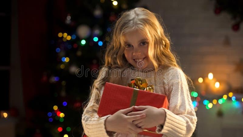 Fille blonde adorable tenant le cadeau de Noël attendu depuis longtemps, regardant la caméra photo libre de droits