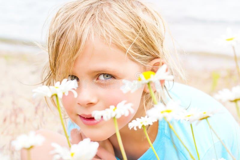Fille blonde assez petite dans une correction des marguerites images stock