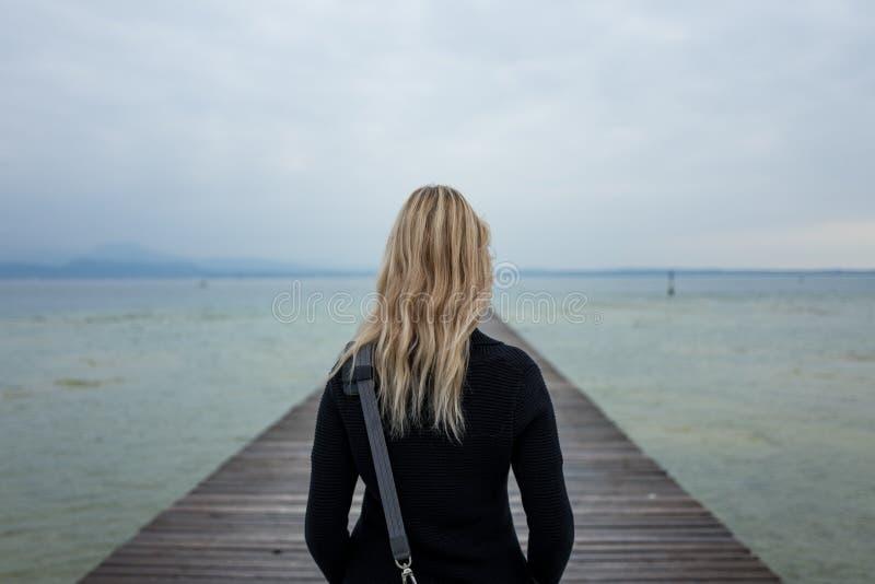 Fille blonde au policier de lac photographie stock libre de droits