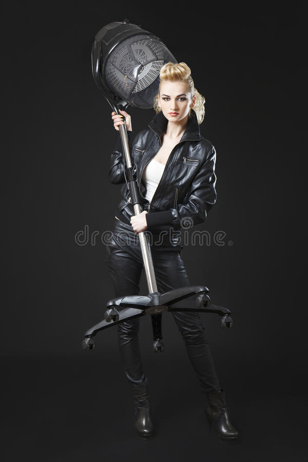 Fille blonde avec l'attitude forte tenant le dessiccateur de salon de beauté photographie stock