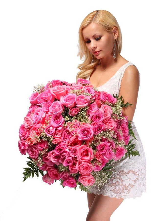 Fille blonde avec le bouquet énorme des roses. Belle jeune femme photos stock
