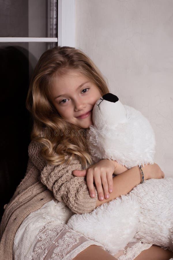 Fille blonde avec le jouet d'ours blanc photos stock