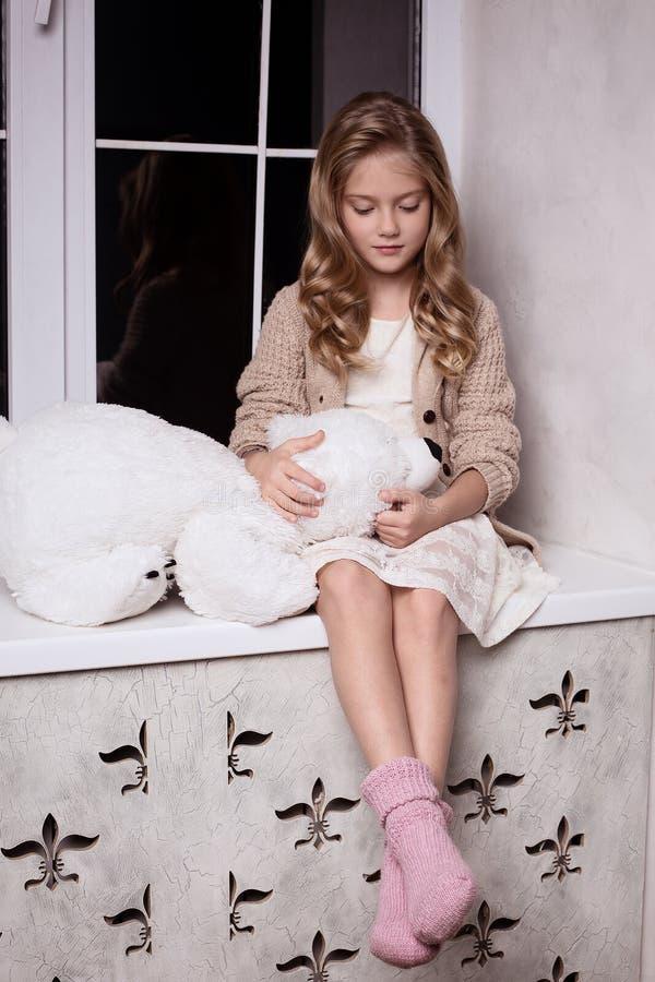 Fille blonde avec le jouet d'ours blanc photos libres de droits