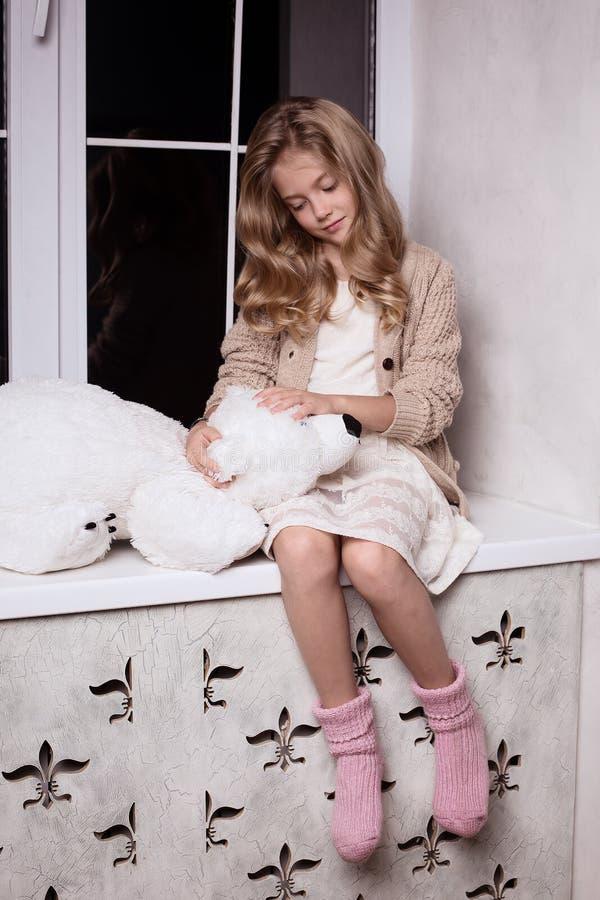 Fille blonde avec le jouet d'ours blanc images stock