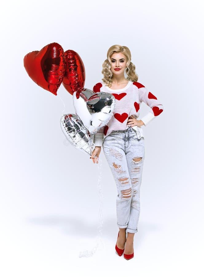 Fille blonde avec les ballons à air rouges de coeurs photo libre de droits