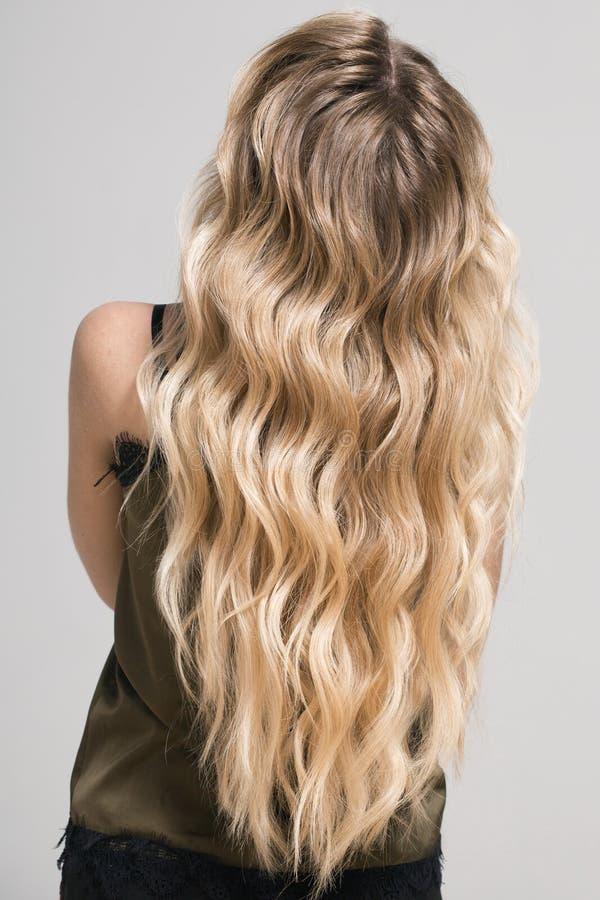 Fille blonde avec longtemps et cheveux onduleux brillants de volume image stock