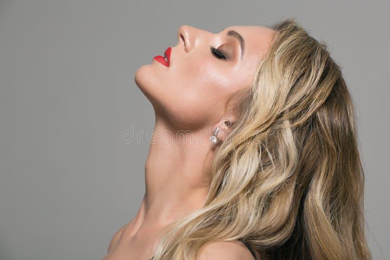Fille blonde avec longtemps et cheveux onduleux brillants de volume images stock