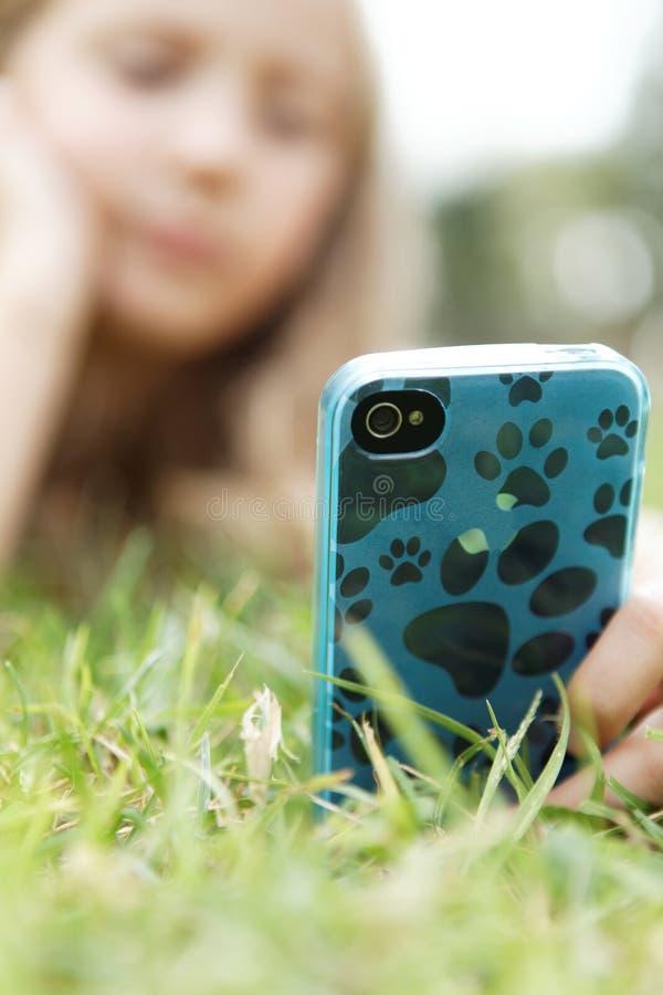 Fille blonde avec un téléphone portable image stock
