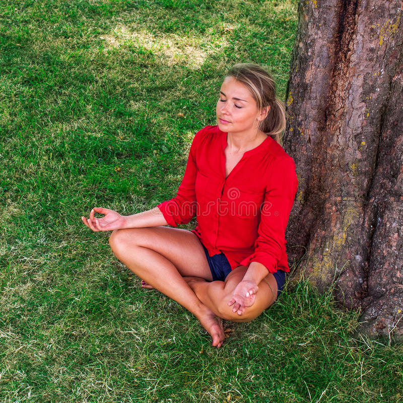 Fille blonde bronzée méditant sous un arbre sur l'herbe photo libre de droits