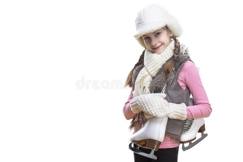 Fille blonde caucasienne adorable et souriante dans des v?tements d'hiver Pose Moiti?-tourn?e avec des patins de glace au-dessus  photos libres de droits
