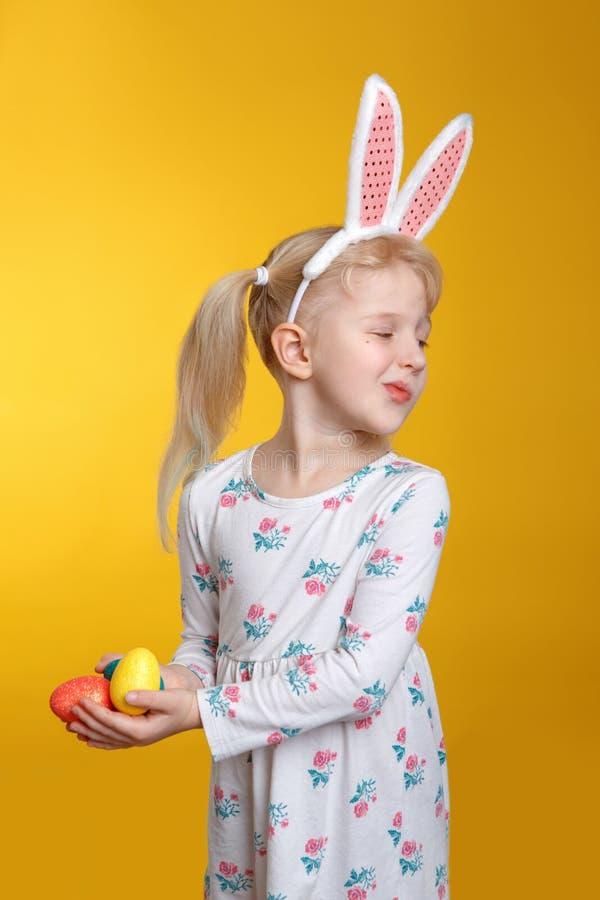 Fille blonde caucasienne dans la robe blanche avec les oreilles roses de lapin de Pâques photo libre de droits