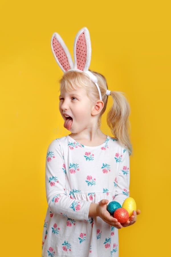 Fille blonde caucasienne dans la robe blanche avec les oreilles roses de lapin de Pâques image stock