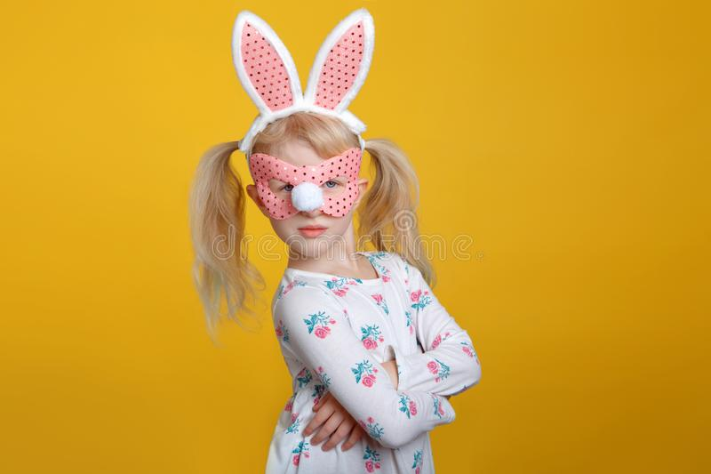 Fille blonde caucasienne dans la robe blanche avec les oreilles roses de lapin de Pâques photographie stock libre de droits