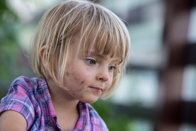 Fille blonde caucasienne de jeune bébé avec le portrait sale de visage à son potager urbain de famille photographie stock libre de droits