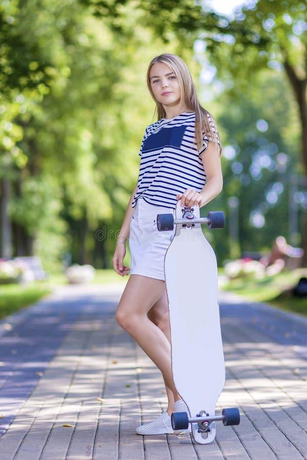 Fille blonde caucasienne de sourire d'adolescent posant avec Longboard dans la région Outdise de parc images libres de droits