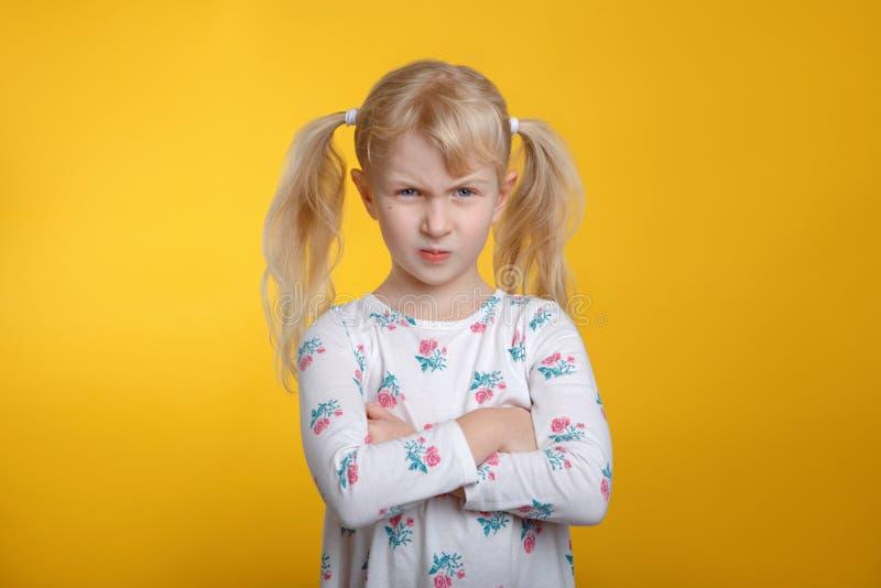 Fille blonde caucasienne fâchée grincheuse avec des yeux bleus dans la robe blanche posant dans le studio sur le fond jaune photographie stock libre de droits