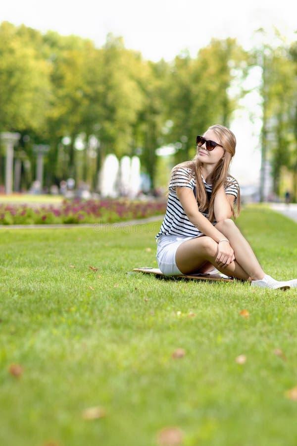 Fille blonde caucasienne positive d'adolescent posant sur Longboard photographie stock