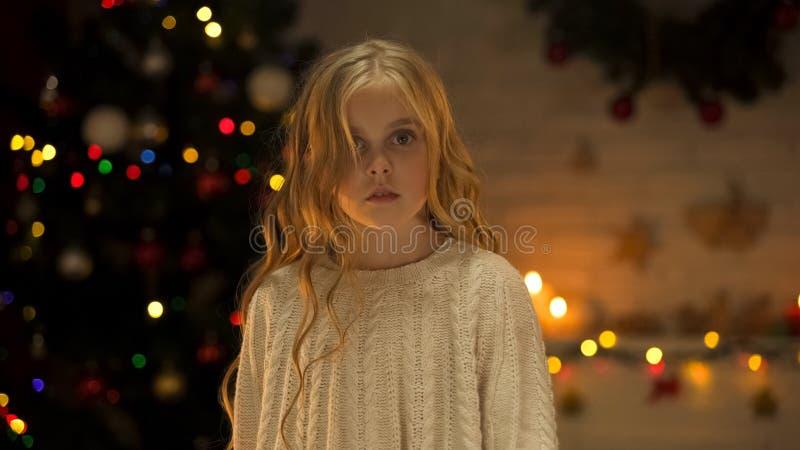 Fille blonde contrariée regardant la caméra, annonce sociale des orphelins abandonnés à Noël photo libre de droits