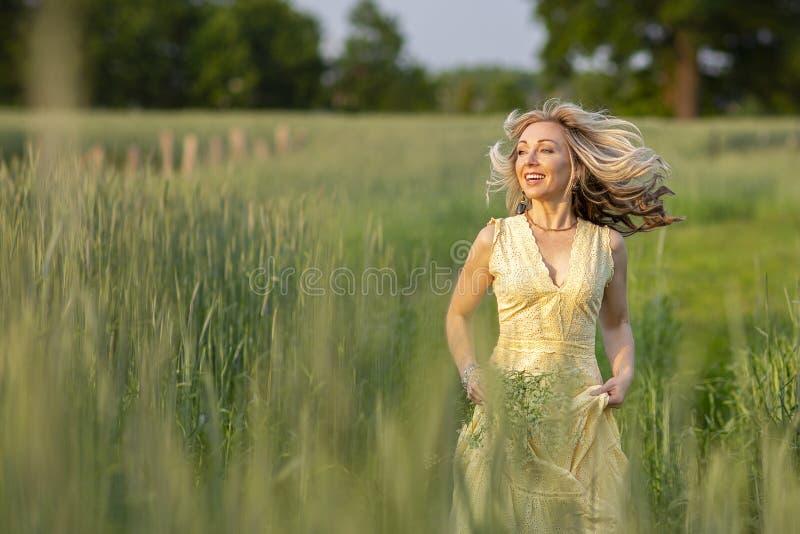 Fille blonde courante sur le champ La vie dans le pays photographie stock