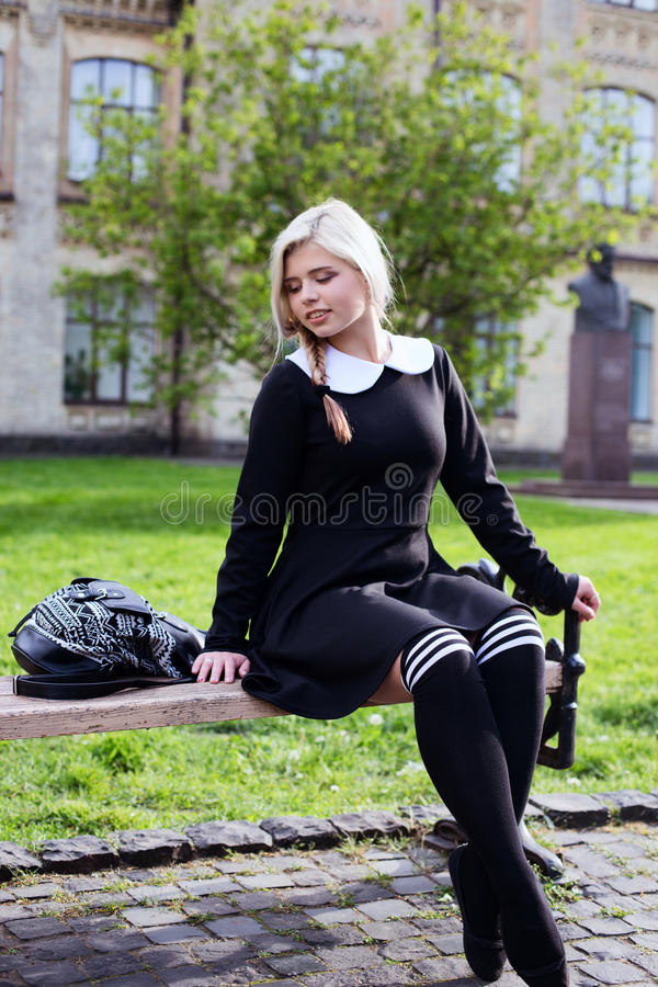 Fille blonde d'étudiant s'asseyant dans la cour de récréation images stock
