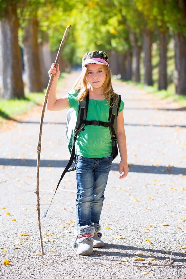 Fille blonde d'enfant d'explorateur marchant avec le sac à dos dans des arbres d'automne image stock