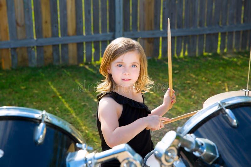 Fille blonde d'enfant de batteur jouant des tambours dans l'arrière-cour de tha photographie stock
