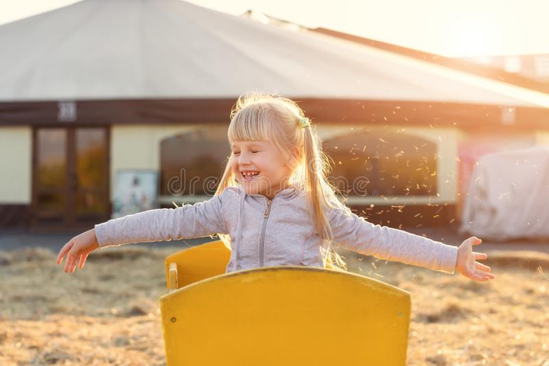 Fille blonde d'enfant de Caucasien mignon adorable s'asseyant dans le chariot en bois ayant la paille ou le foin de lancement d'a image libre de droits