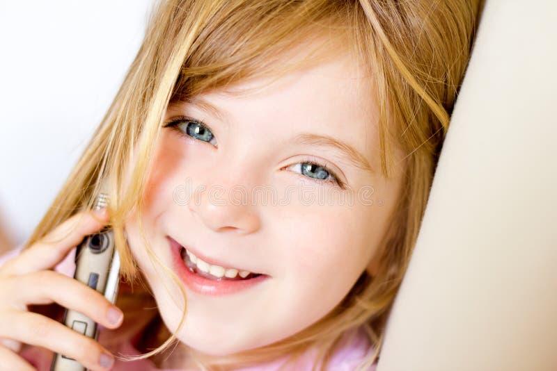 Fille blonde d'enfant parlant le mobilophone image stock
