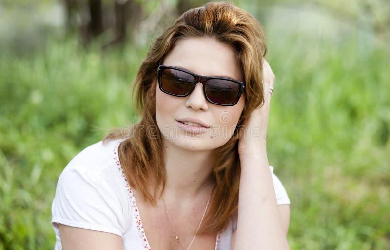 Fille blonde dans des lunettes de soleil au stationnement d'été. photographie stock libre de droits