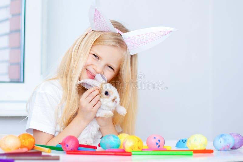 Fille blonde dans des oreilles de lapin sur la tête et petit lapin dans des ses mains Oeufs et marqueurs colorés sur la table Pre photos stock