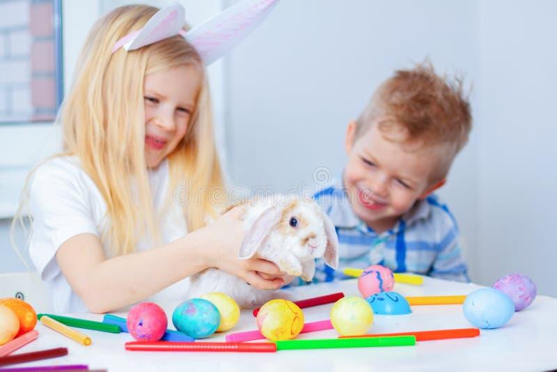 Fille blonde dans des oreilles de lapin sur le chef et le garçon avec peu de lapin Oeufs et marqueurs colorés sur la table Prepea images stock