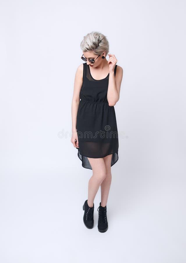 Fille blonde dans la robe noire sur le fond blanc photos stock