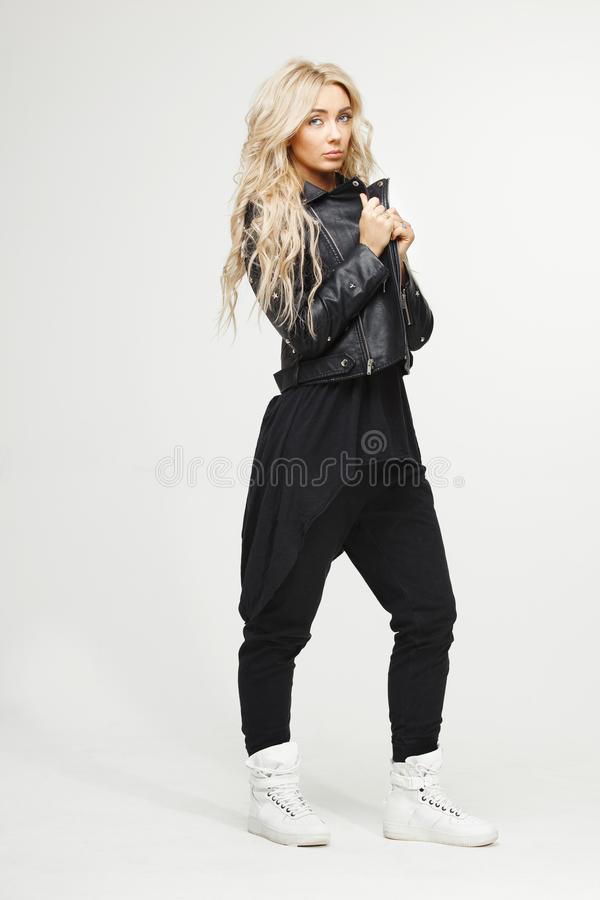 Fille blonde dans la veste noire et le long T-shirt avec des jeans sur le fond blanc de studio photos libres de droits