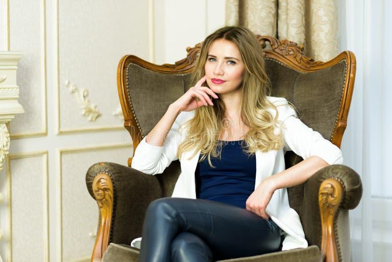Fille blonde dans le pantalon en cuir se reposant dans un divan image libre de droits