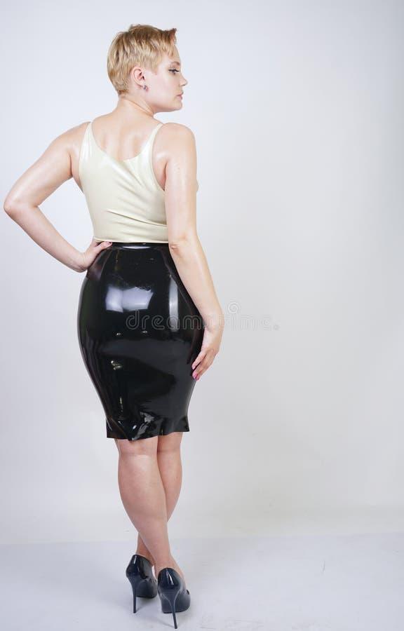 Fille blonde de cheveux rouverains avec la robe en caoutchouc de port de latex de corps sinueux sur le fond blanc de studio photo stock