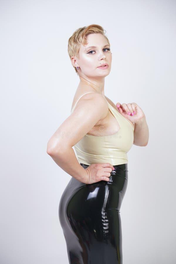 Fille blonde de cheveux rouverains avec la robe en caoutchouc de port de latex de corps sinueux sur le fond blanc de studio images libres de droits